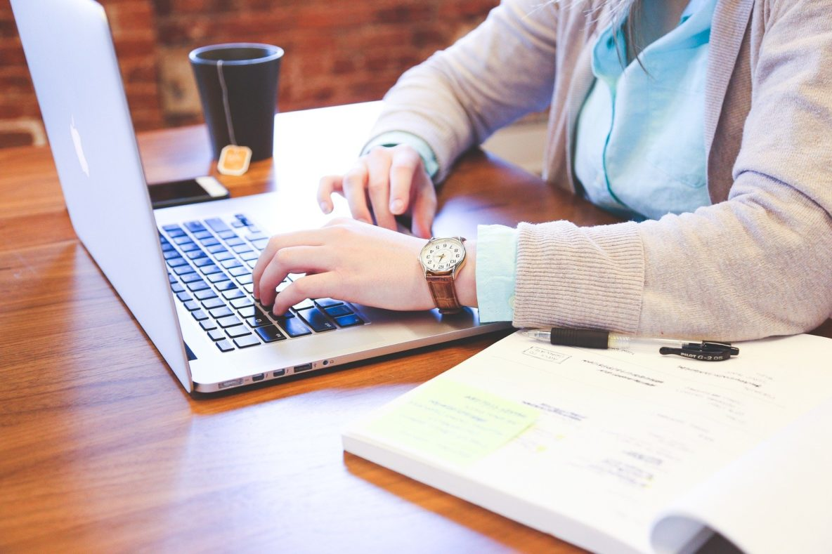 Close up of woman's arms and hands on laptop at table